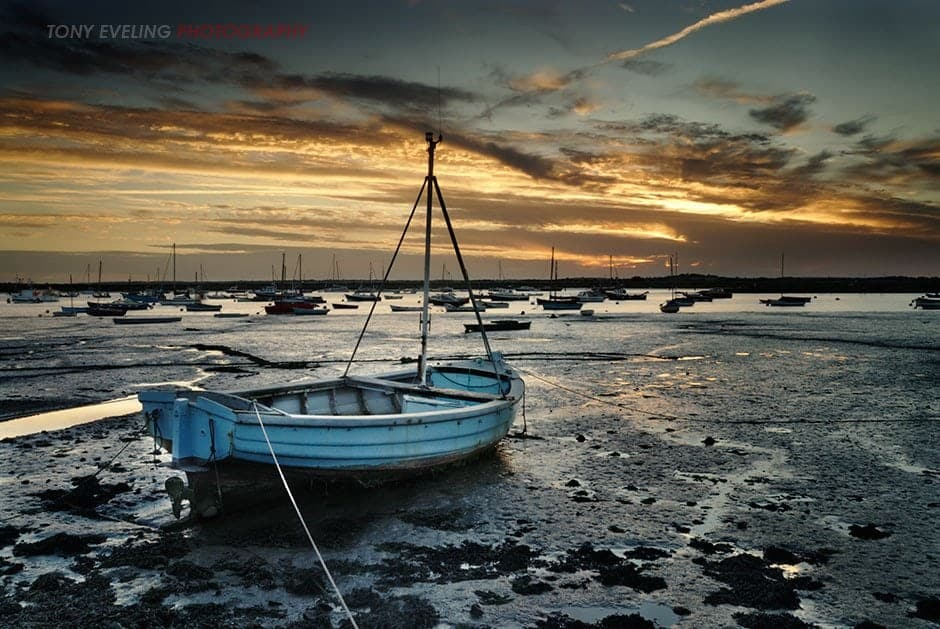 Boats moored at low tide, Mersea Island, Essex, England, UK
