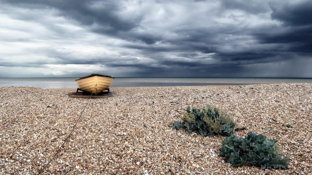 Yellow boat on the beach against a stormy sky