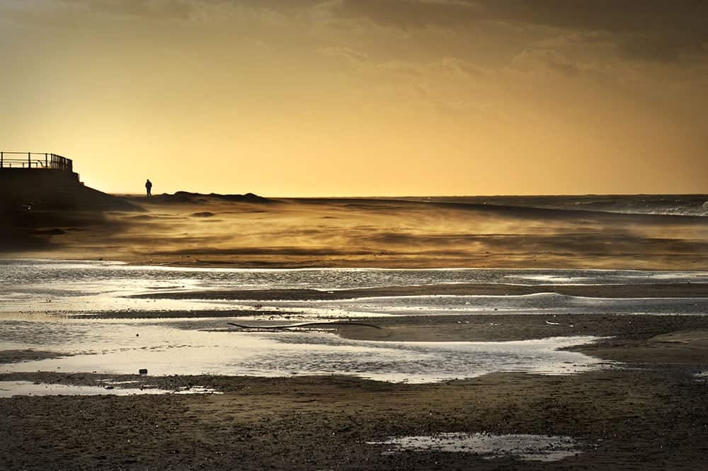 Lone figure walking on the beach, against a warm orange sky. Ostend, Belgium