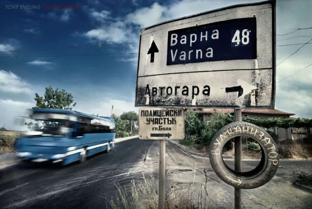 Road sign and a passing bus, just south of Varna, on the coastal road.  Bulgaria