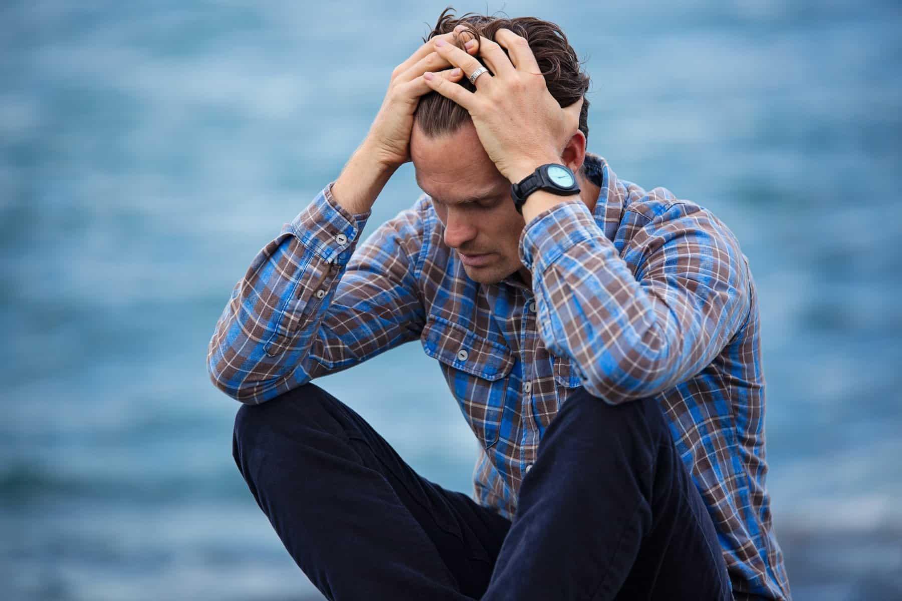 Homem de meia idade arrependido, sentado no chão com as mãos na cabeça