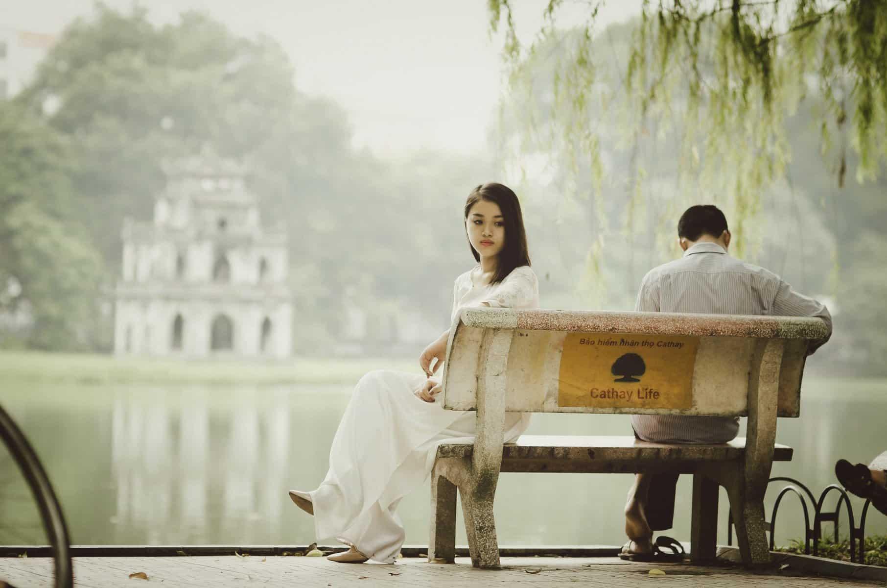 Casal sentado separadamente em banco no parque