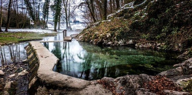 سلوفينيا - Dolenjska - بركة ينبوع ساخن مع منظر طبيعي ثلجي في الخلفية.
