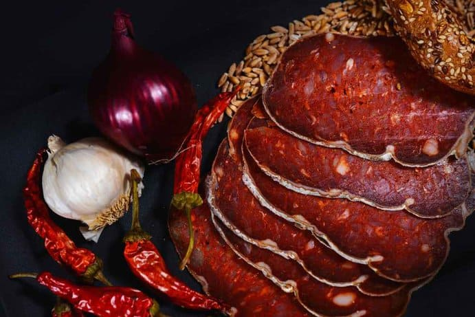 beautifully pieces of kulen on a black plate with onion and chili in a black background. closeup