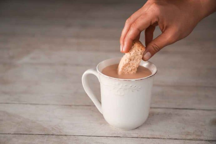 Croatia - Woman's hand dipping a delicious rusk in hot coffee