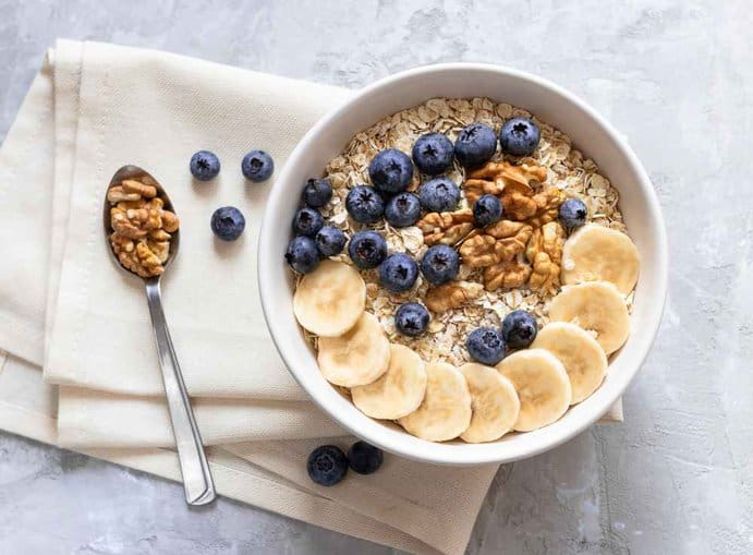 Croatia - Oatmeal. Porridge with bananas, blueberries and walnut for healthy breakfast or lunch. Natural ingredients. Flat lay design on linen napkin and cement background