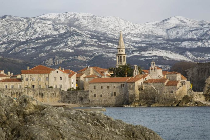 Montenegro - Budva - Ocean and city of Budva with snow covered mountains in background