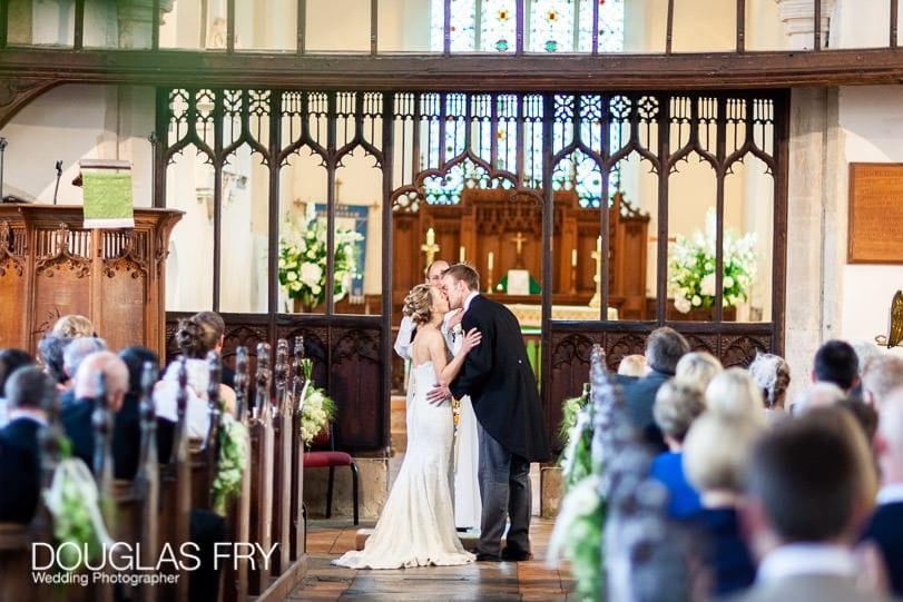 wedding photographer norfolk church - couple kissing