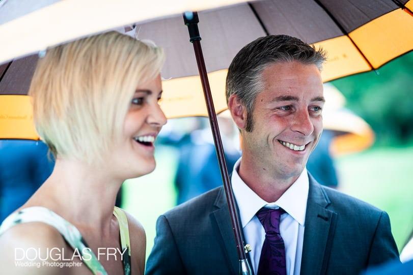 Couple under umbrella at Coworth Park