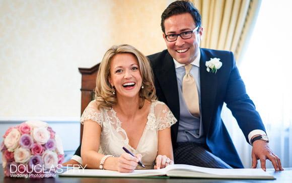 Wedding photographer - couple signing register in Chelsea Register office