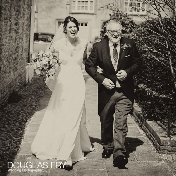 Bride and Father walking to Church down path - black and white photograph