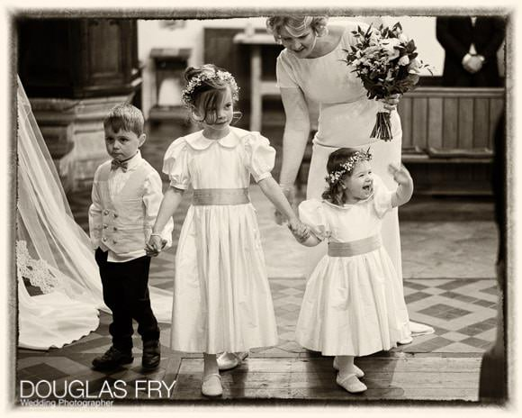 Bridesmaids and page in church with one waving to the congregation