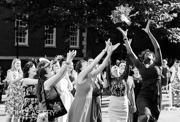 Bridesmaid catching bouquet in Chelsea - black and white wedding photograph
