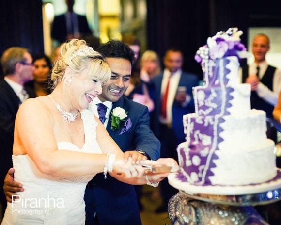 bride and groom cutting wedding cake in London