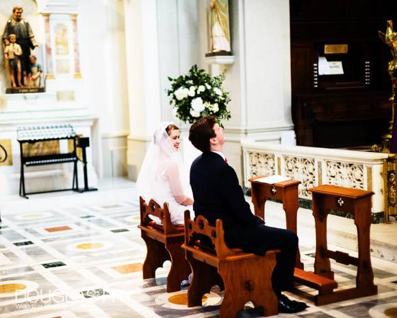 Bride and groom sitting in church during ceremony in Soho, London