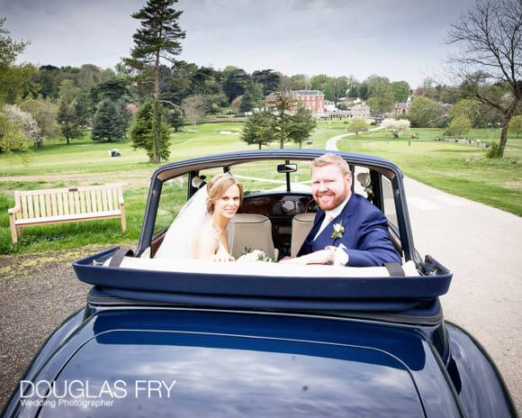 Bride and groom in car in front of RAC Epsom