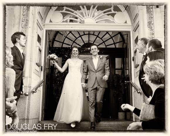 Wedding photograph on steps of Chelsea Register Office after ceremony with confetti and friends and family