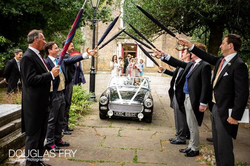 London wedding photographer leaving by car through umbrellas arch