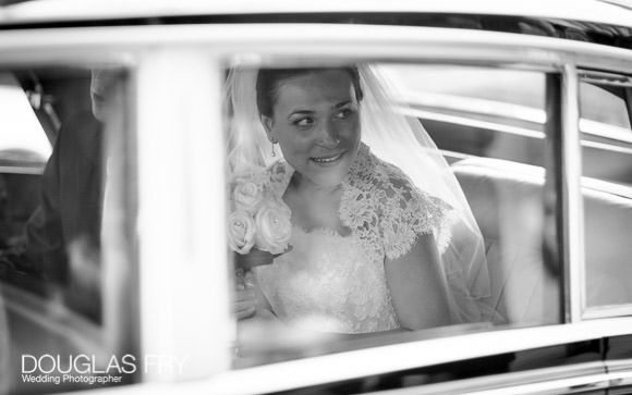 Bride photographed in car leaving ceremony