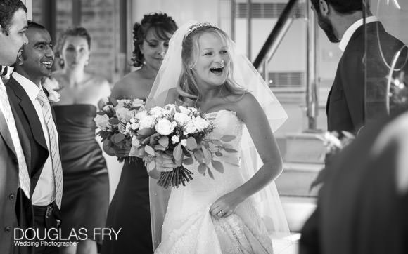 Bride laughing as she arrives at HTB for her wedding - photographed by Douglas Fry