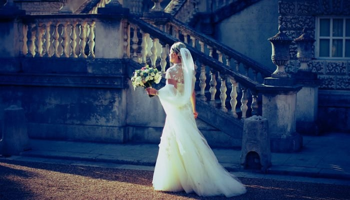 Beautiful bride photographed with her bouquet in front of Chiswick House.