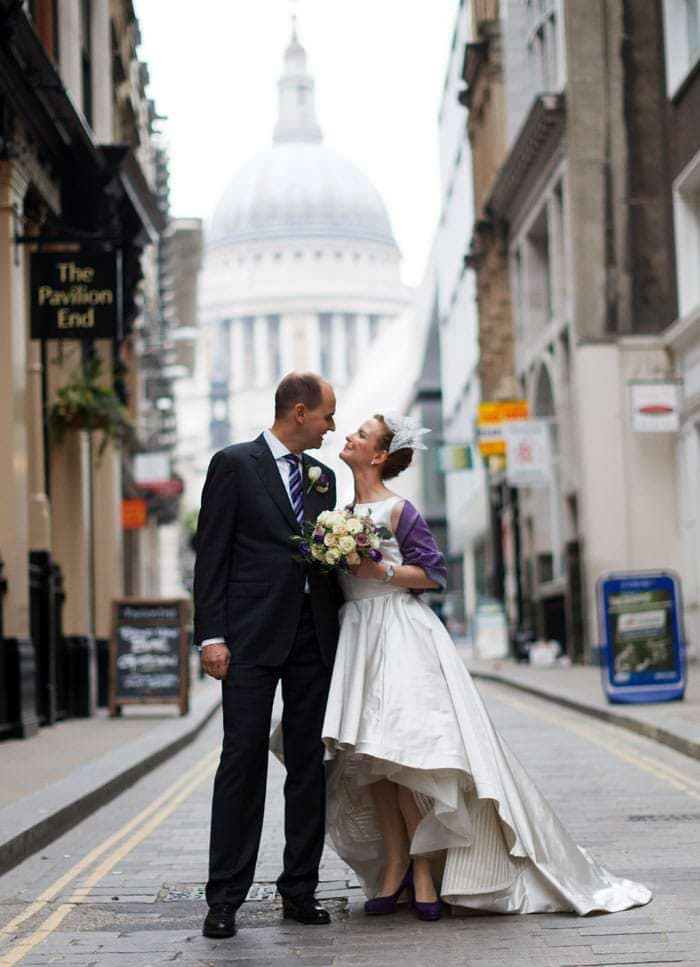 Wedding photograph of bride and groom outside in London with St Paul's in background