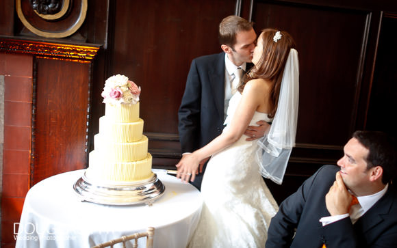 wedding photograph of bride and groom kissing after cutting the wedding cake