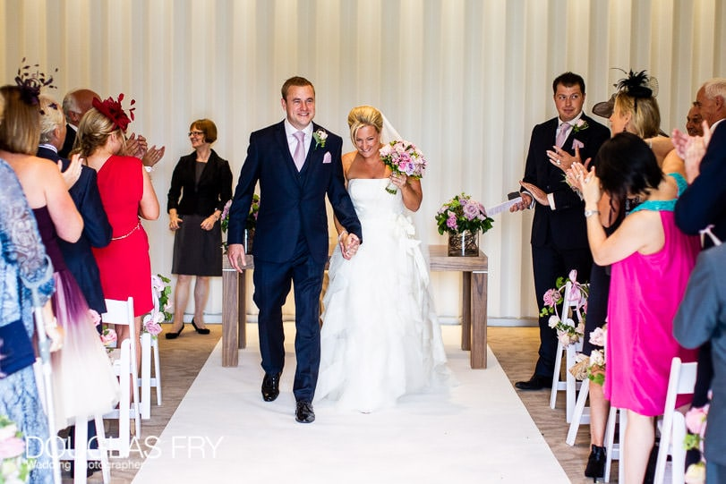 Couple walking down aisle after wedding ceremony at Coworth Park