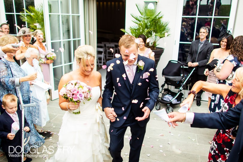 Confetti being thrown photographed during wedding at Coworth Park