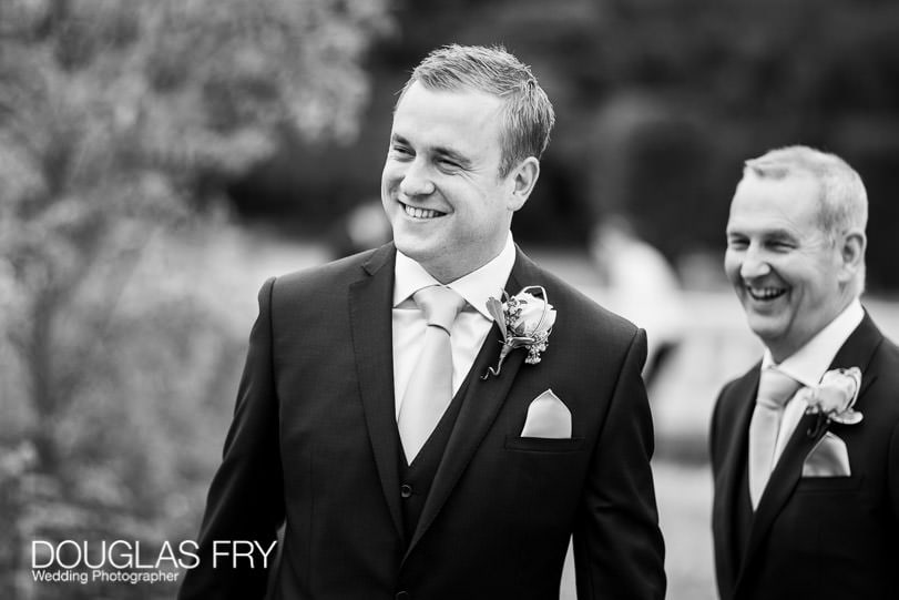 Groom photographed in black and white at gardens of Coworth House
