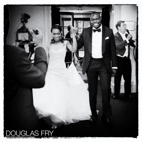 Bride and groom entering the wedding reception - black and white photograph