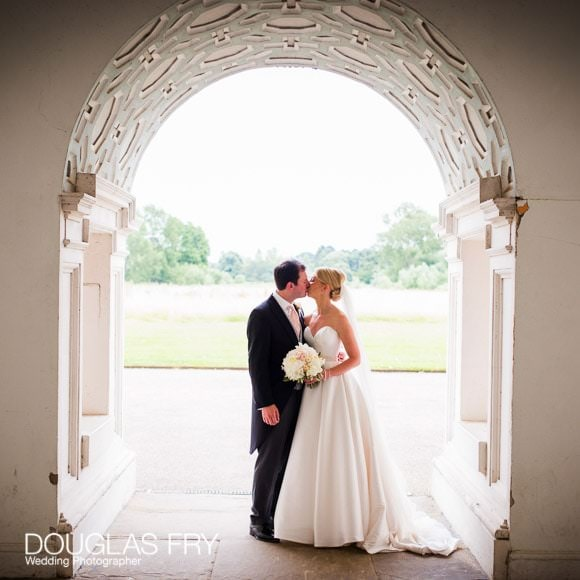 Bride and groom kissing under arch at Syon House