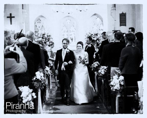 Bride and groom leaving church in black and white