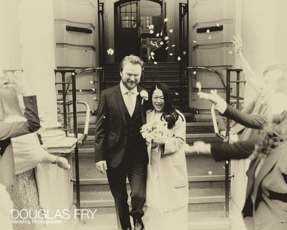 Black and White photograph with confetti as bride and groom leave register office in London