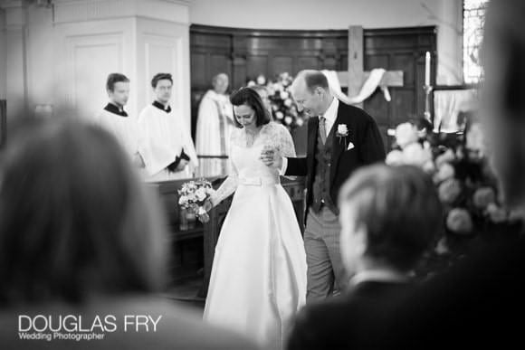 Black and white photograph of bride and groom in church in Battersea - walking down aisle