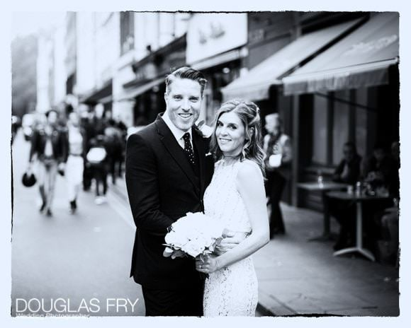 black and white photograph of bride and groom in London street in front of cafe