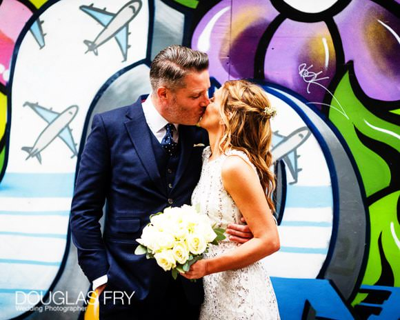 Couple kissing in front of London mural / graffiti