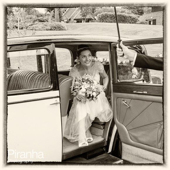 Bride getting out of car at Worth Abbey