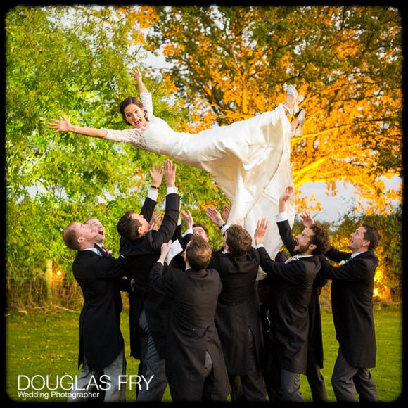 Bride being thrown in air by ushers during photographs