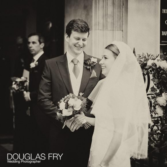 Black and white photograph of bride and grooming leaving church
