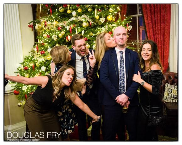 In and Out Club wedding photograph of guests in front of Christmas tree