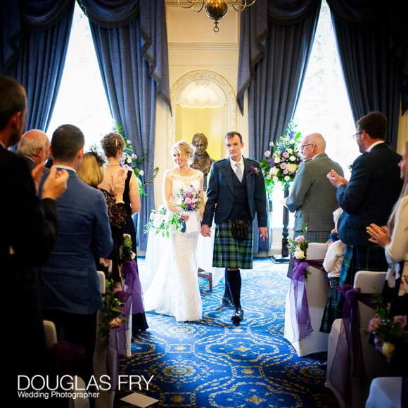 The bride and groom walking down the aisle at the Caledonian Club at the end of the wedding ceremony