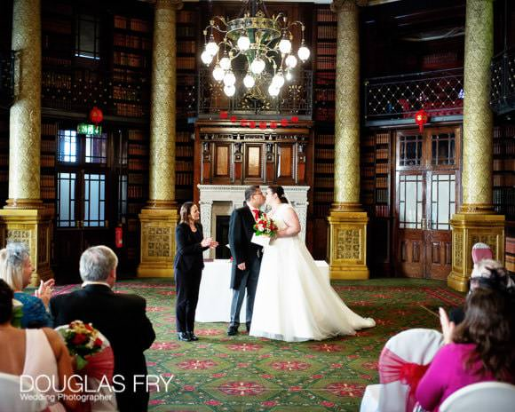 Bride and groom kissing at end of wedding ceremony