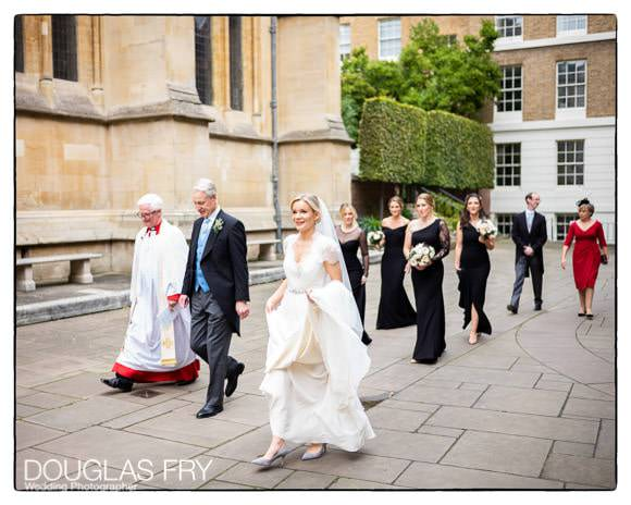 Bride with father and bridesmaids walking towards entrance to Temple Church