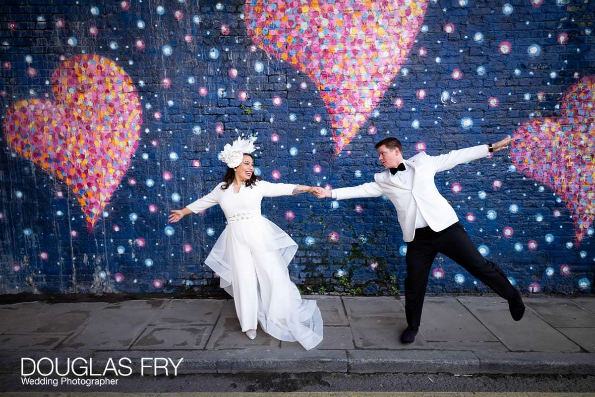 Bride and groom photographed in front of London Mural