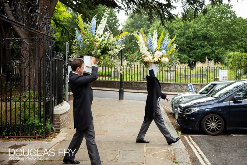 ushers carrying flowers to the reception restaurant in London