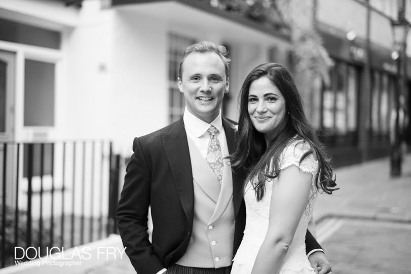 couple photographed together in front of Londo restuarant by Douglas Fry Wedding Photographer London