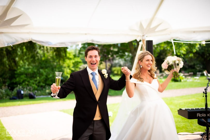 wedding photograph of bride and groom entering marquee