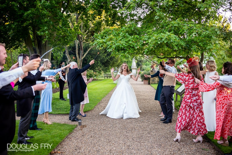 Bride leaving wedding reception photographed with sparklers